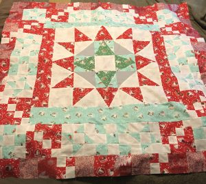 After many starts a stops I have finally completed the Holiday Mystery Quilt. Also my first quilt to